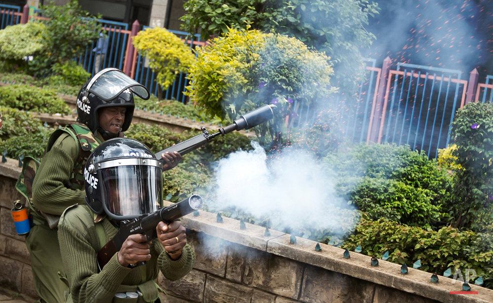 Kenyan police fire tear gas to disperse a small group of opposition protesters who tried to gather outside the offices of the electoral commission, in downtown Nairobi, Kenya Monday, May 23, 2016. Kenya's police shot, beat and tear gassed opposition demonstrators across the country who tried to gather to call for the electoral commission to be dissolved due to allegations of bias and corruption. (AP Photo/Ben Curtis)