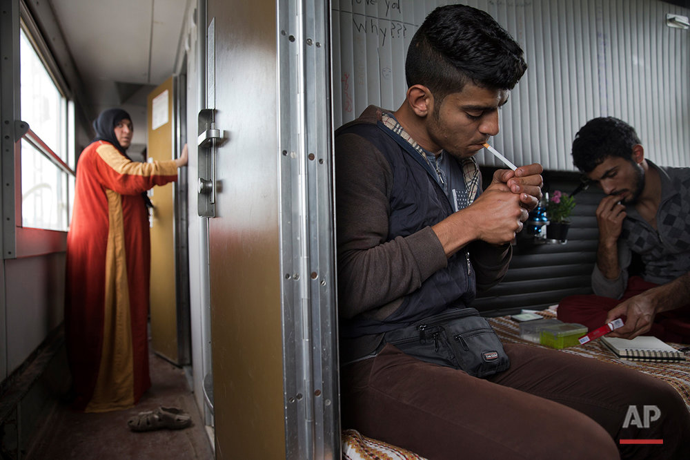 In this Sunday, May 8, 2016 photo, 23-year-old-Syrian man Mohamed lights a cigarette in his cousins cabin Majd Hamid , 22, as a Syrian woman Fatme gets in her  cabin inside a train car that they live in, in the sprawling refugee and migrant tent city if Idomeni, on Greece's northern border with Macedonia. (AP Photo/Petros Giannakouris)