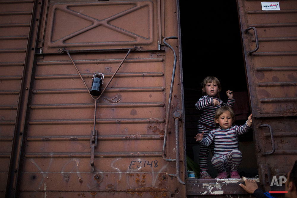 In this Tuesday, May 10, 2016 photo two Syrian twin sisters chat with a relative as they stand inside a freight car that their family live in the sprawling refugee and migrant tent city of Idomeni, on Greece's northern border with Macedonia. On government orders, Idomeni was cleared this week. Just before the evacuation Idomeni had 8,400 occupants, according to official figures, and it's unclear where all those who didn't get the buses to other camps are. (AP Photo/Petros Giannakouris)