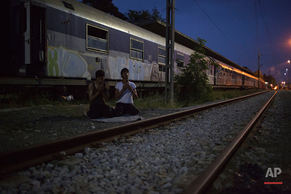 In this Tuesday, May 10, 2016 photo, two Afghan man pray near railway track in front of the train that they live in the sprawling refugee and migrant tent city of Idomeni, on Greece's northern border with Macedonia. (AP Photo/Petros Giannakouris)