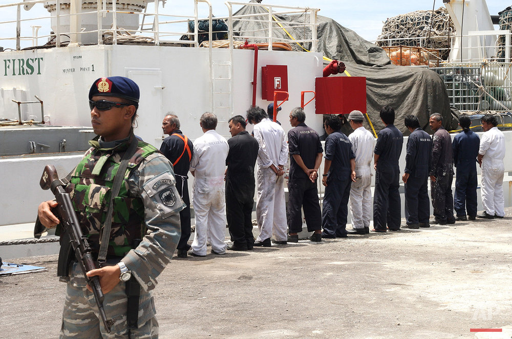 Navy personnel stand guard as the crew of Silver Sea 2, a Thai-owned cargo ship which was seized by Indonesian authorities last August, are lined up during a media conference at the port of Sabang, Aceh province, Indonesia, Friday, Sept. 25, 2015. The Thai captain of the ship has been arrested in Indonesia following allegations of illegal fishing, an official said Friday. It is the latest development linked to an Associated Press investigation that uncovered a slave island earlier this year. (AP Photo/Heri Juanda)