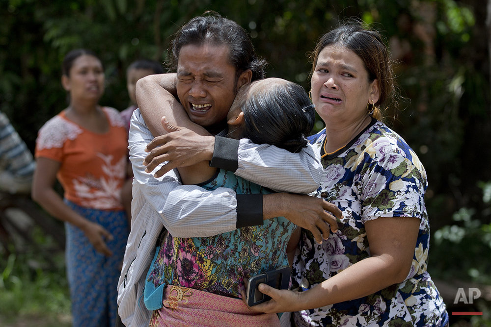 In this May 16, 2015, photo, former slave fisherman Myint Naing, left, is embraced by his mother Khin Than, second left, as his sister Mawli Than, right, is overcome with emotion after they were reunited after 22 years in their village in Mon State, Myanmar. Myint, 40, is among hundreds of former slave fishermen who returned to Myanmar following an Associated Press investigation into the use of forced labor in Southeast Asia's seafood industry. (AP Photo/Gemunu Amarasinghe)
