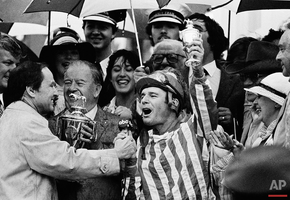 Eddie Delahoussaye in the winner's circle raises a trophy in victorious salute after guiding Sunny's Halo to victory in the Kentucky Derby at Churchill Downs on Saturday, May 7, 1983 in Louisville, Ky. (AP Photo)