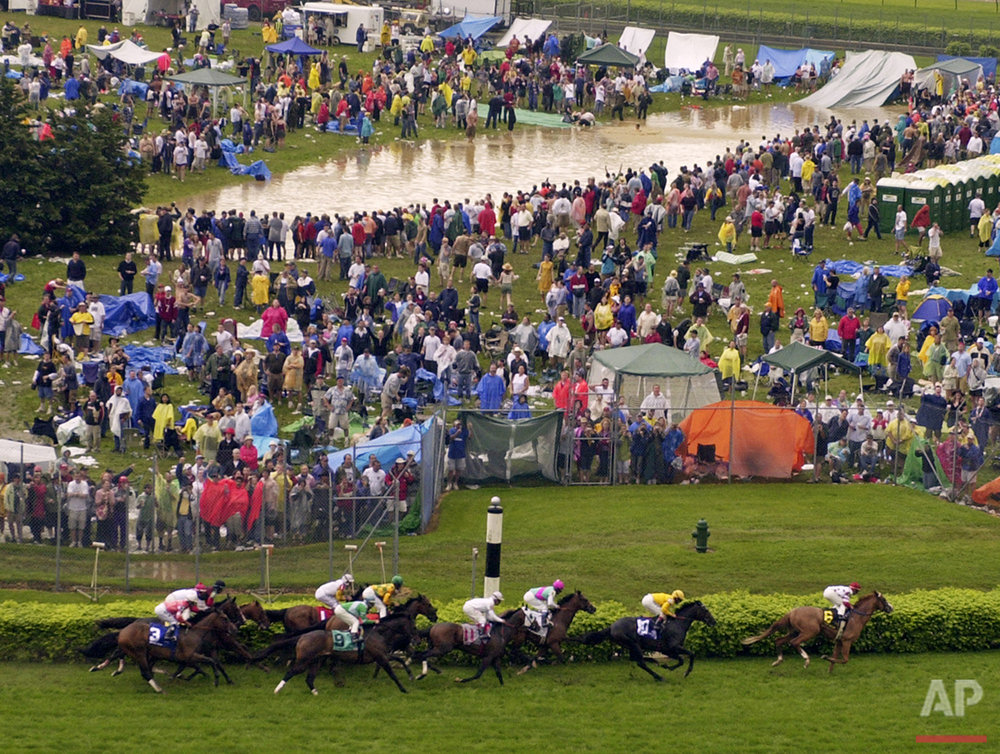 The field from the ninth race makes its way around the turn as revelers swim in a catch-basin in the infield at Churchill Downs after a sudden downpour flooded the track and infield during Kentucky Derby day festivities, Saturday, May 1, 2004, in Louisville, Ky. (AP Photo/Darron Cummings)