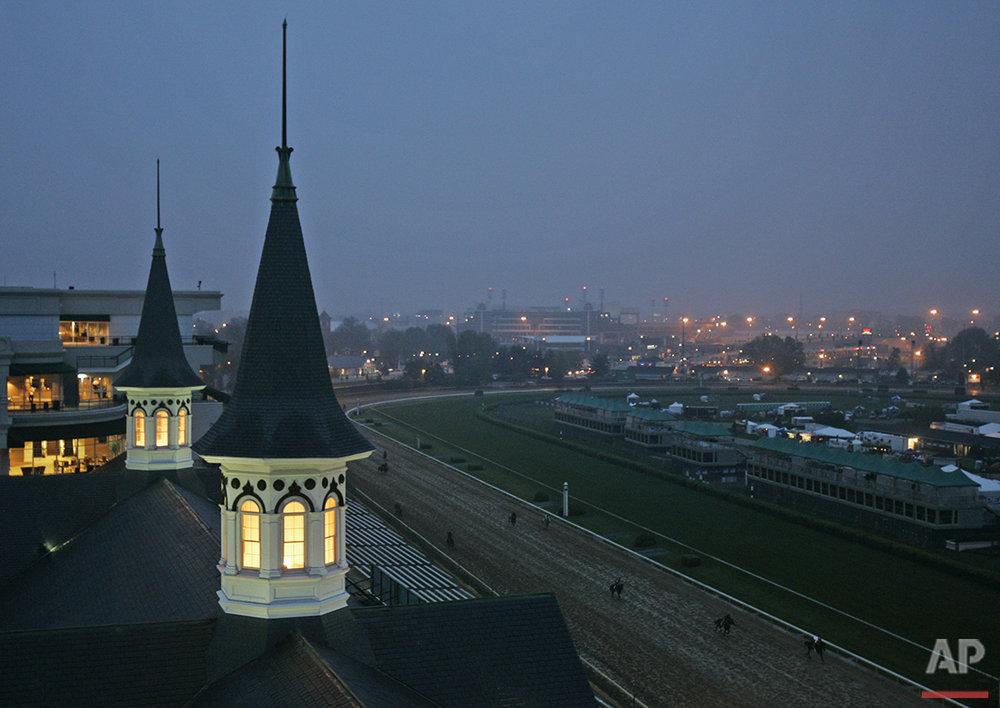 Horses run past the Churchill Downs spires in Louisville, Ky., Friday, May 4, 2007. (AP Photo/Darron Cummings)