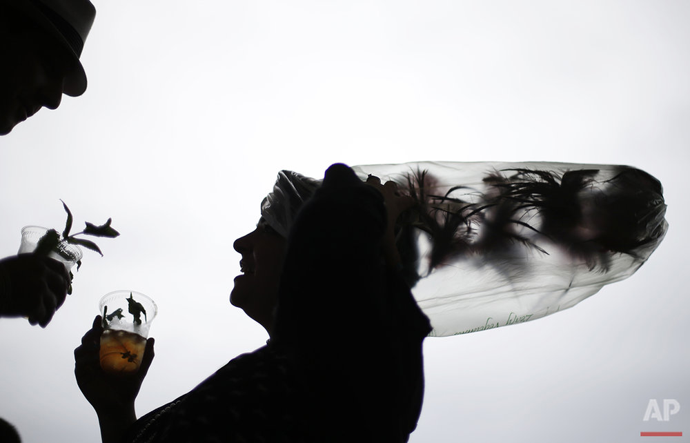 Desirae Masterson, of Indianapolis, with her hat covered in a plastic bag to protect it from the rain, shares a mint julep with her husband, Ray, before the running of the 139th Kentucky Derby at Churchill Downs Saturday, May 4, 2013, in Louisville, Ky. (AP Photo/David Goldman)