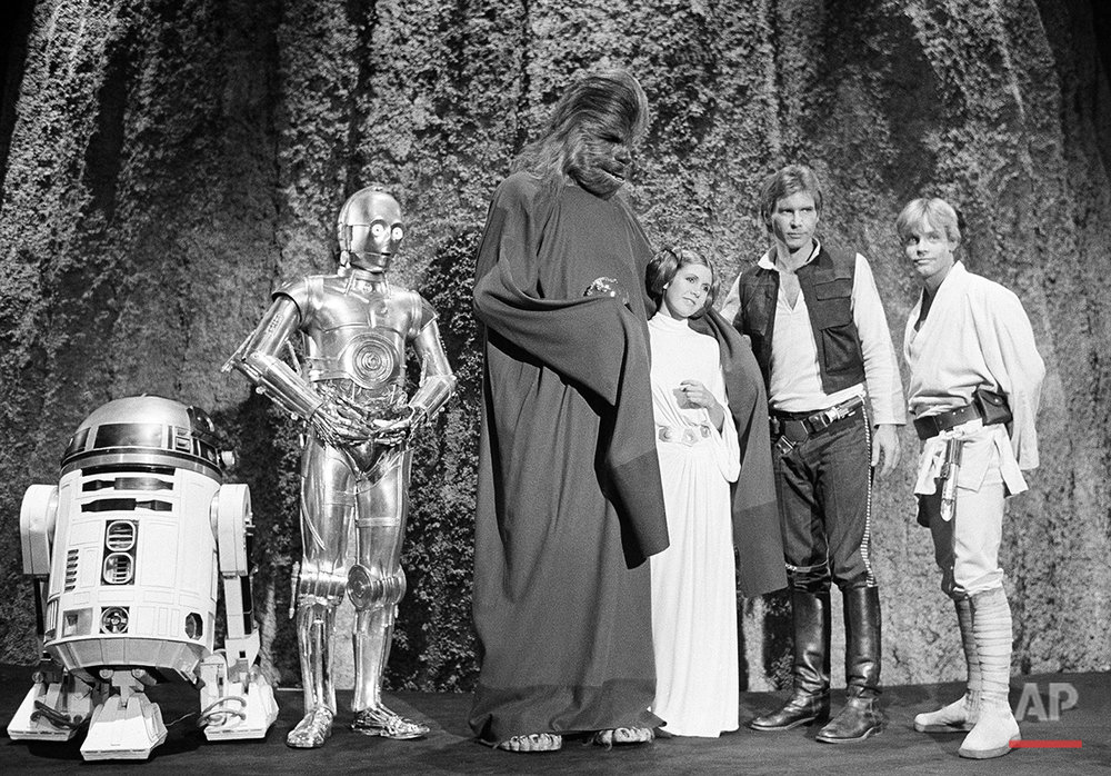 """Harrison Ford, as Han Solo of """"Star Wars"""" with Carrie Fisher in the filming of the CBS-TV special """"The Star Wars Holiday"""" Nov. 13, 1978. Ford says he leaves the singing in the special to Carrie, who is the daughter of Eddie Fisher and Debbie Reynolds. The film will also feature many special effects not seen on the original movie. (AP Photo/George Brich)"""