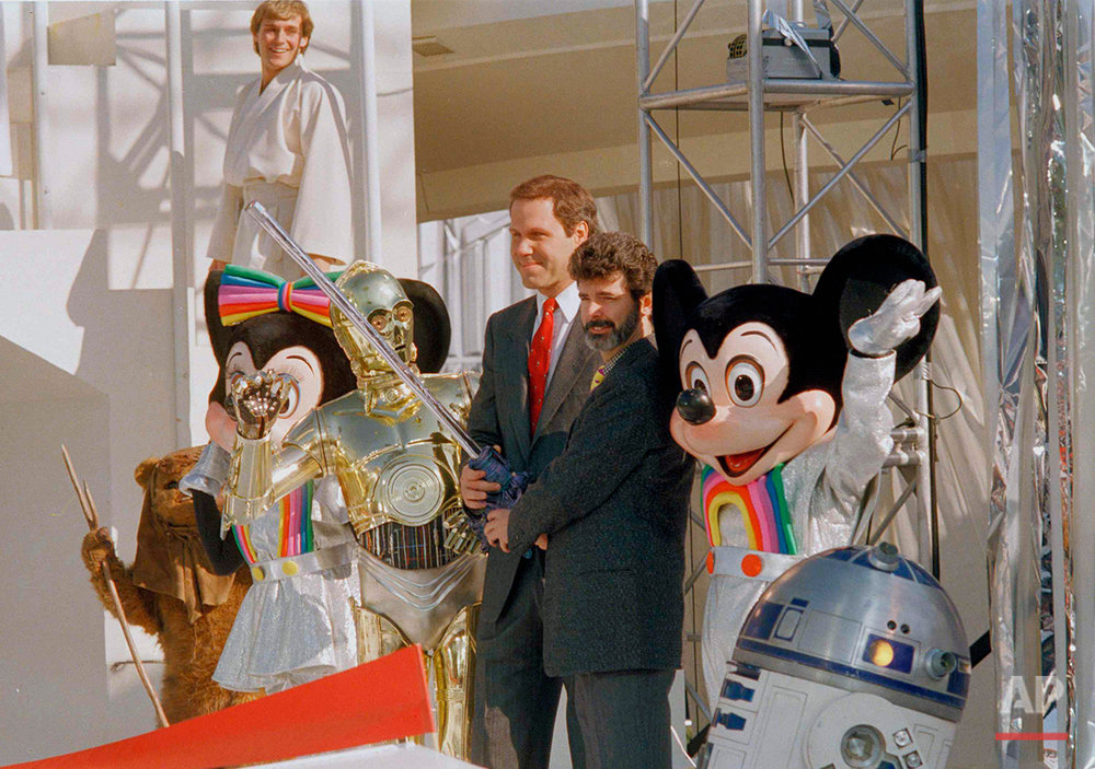 """Michael Eisner, center, Disney chairman, and """"Star Wars"""" creator George Lucas (with beard) prepare to use a light saber to cut the ribbon to open the new """"Star Tours"""" attraction at Disneyland in Anaheim, Calif., Jan. 9, 1987.  The ride careens people on a spaceship through a star-dodging trip into cinematic outer spac.  Characters, from left, are Minnie Mouse, C-3PO, Mickey Mouse and R2-D2.  (AP Photo/Bob Galbraith)"""