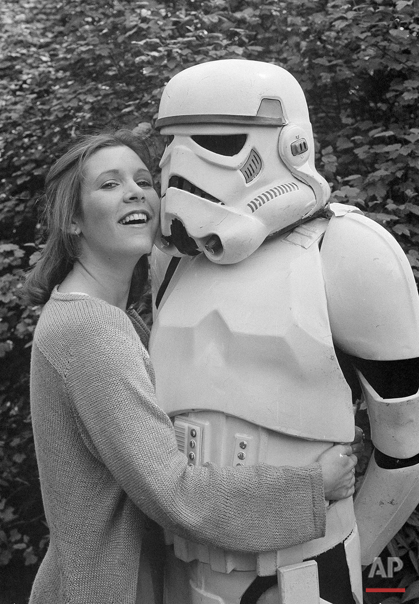 """American actress Carrie Fisher, star of the movie """"The Empire Strikes Back,"""" sequel to the record-breaking """"Star Wars"""" epic, cuddles up to a Stormtrooper in a London park, May 23, 1980. They were in London to promote the movie. (AP Photo/Dave Caulkin)"""