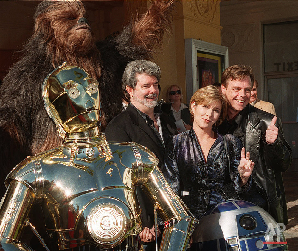 """Characters from the film """"Star Wars"""" join writer and director George Lucas, left, Carrie Fisher, center, and Mark Hamill at the world premiere of """"Star Wars Special Edition"""" Saturday, Jan. 18, 1997, in the Westwood section of Los Angeles.  The movie  was first released 20 years ago. (AP Photo/Rene Macura)"""