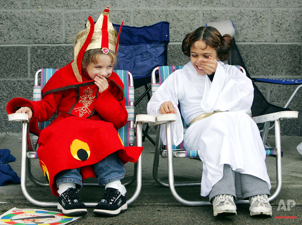 """Aurora Olayos, left, 6, dressed as Queen Amidala, shares a laugh with sister Ariel Olayos, 9, right, dressed as Princess Leia, as they sit outside the Lloyd Cinemas waiting for the opening of """"Star Wars: The Revenge of the Sith"""" in Portland, Ore., Wednesday, May 18, 2005.  Both girls won tickets to the grand opening of the movie with their costumes. The movie opens nationwide, Thursday. (AP Photo/Don Ryan)"""