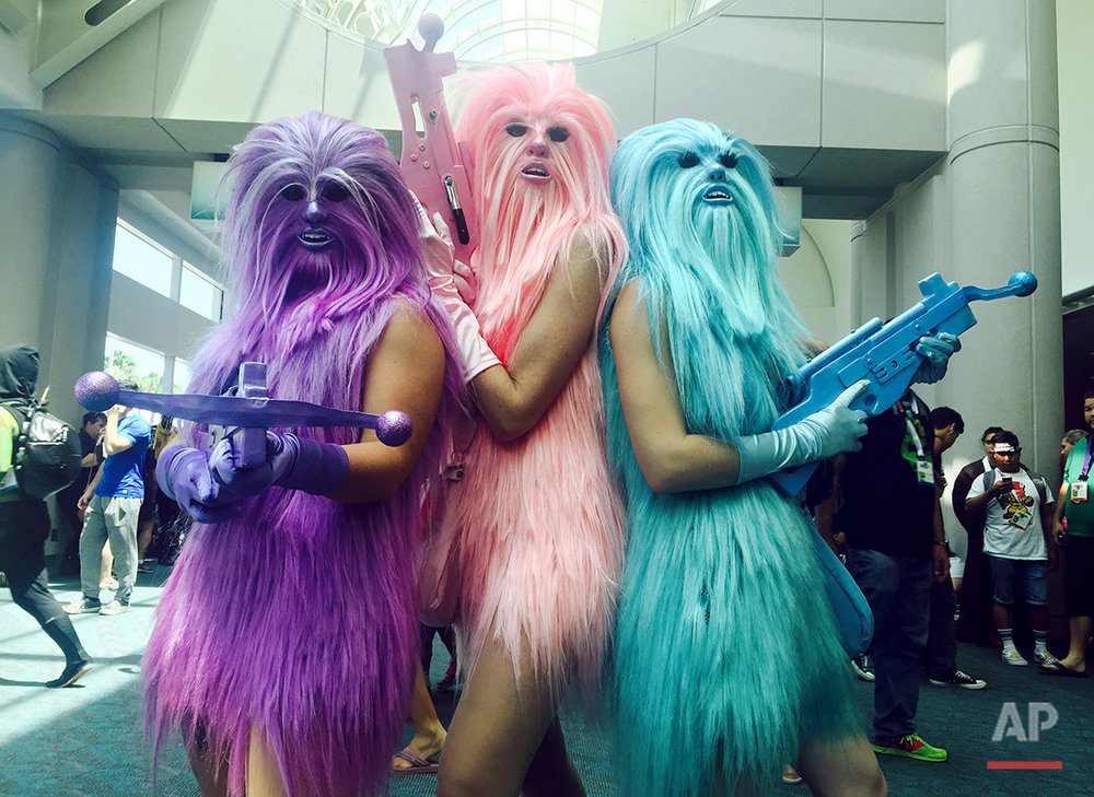 """In this July 10, 2015 photo, fans dressed as """"Chewie's Angels"""" attend day 2 of Comic-Con International, in San Diego, Calif. Star Wars"""" inspires curiously personal reactions. It drives some people to don Wookie costumes and others to curse an entire industry as infantile. Since the 1977 debut of """"A New Hope,"""" it's become a generational rite of passage not just to experience the saga, but to form one's relationship with movies around it, whether in happy lockstep or rebel opposition. (Photo by Chelsea Vicari/Invision/AP)"""