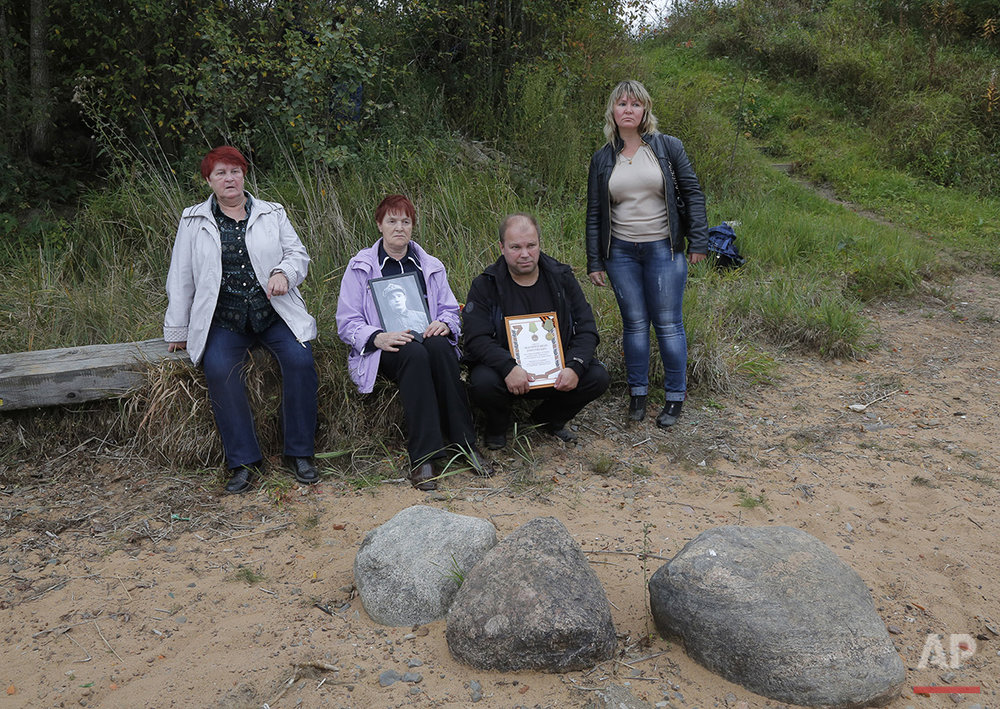 In this photo taken on Friday, Sept. 18, 2015, Tamara Zhukova, left,  and Zoya Izotova, second left, sit at the place where remains of their relatives, Soviet soldiers, were uncovered, at Nevsky Pyatachok near Kirovsk, Russia. Nevsky Pyatachok. The area about 50 kilometers (30 miles) southeast of St. Petersburg, has proved especially fertile ground. As many as 200,000 Soviet soldiers were killed here between September 1941 and May 1943 in fighting to break the Nazi siege of the city, which was then called Leningrad.  (AP Photo/Dmitri Lovetsky)