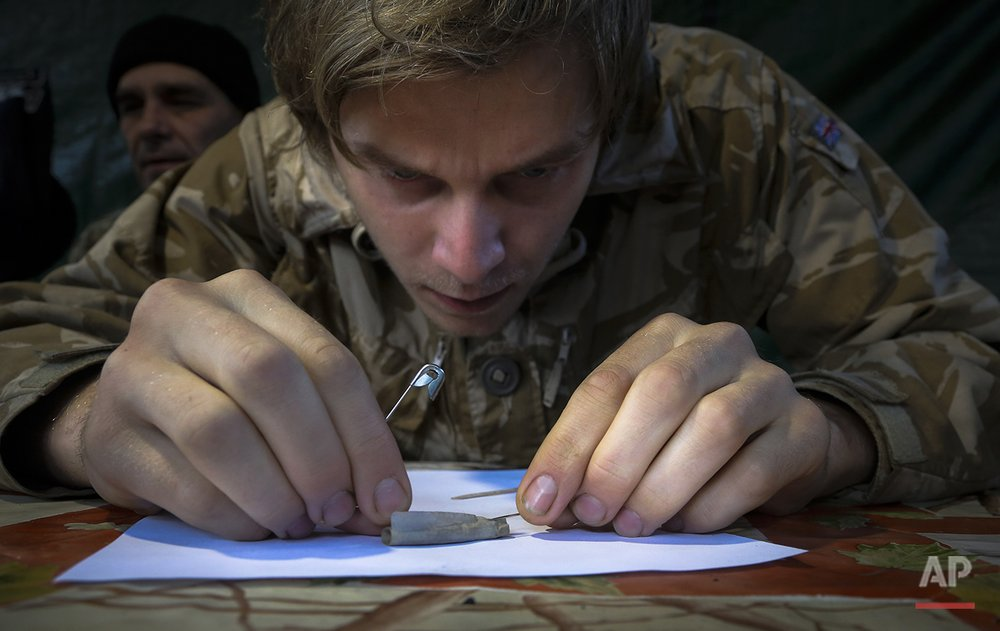In this photo taken on Sunday, Sept.  20, 2015 Artem Goryachev, a member of a volunteer group searching for the remains of Soviet soldiers killed during WWII, rolls out a paper found inside a dog tag uncovered among remains at  Nevsky Pyatachok near Kirovsk, Russia. Nevsky Pyatachok, an area about 50 kilometers (30 miles) southeast of St. Petersburg, has proved especially fertile ground. As many as 200,000 Soviet soldiers were killed here between September 1941 and May 1943 in fighting to break the Nazi siege of the city, which was then called Leningrad.  (AP Photo/Dmitri Lovetsky)
