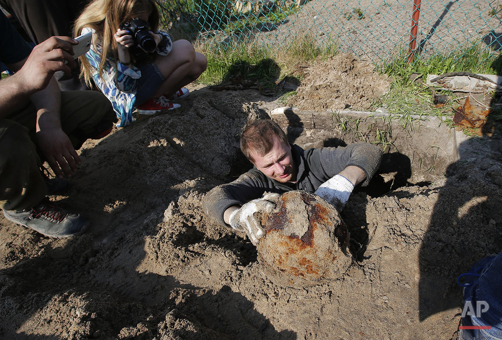 In this photo taken on Tuesday, May  3, 2016,  a member of a volunteer group searching for the remains of Soviet soldiers killed during WWII,  uncovers a helmet of a  Soviet soldier at the yard of a private house at Nevsky Pyatachok near Kirovsk, Russia. Nevsky Pyatachok. The an area about 50 kilometers (30 miles) southeast of St. Petersburg, has proved especially fertile ground. As many as 200,000 Soviet soldiers were killed here between September 1941 and May 1943 in fighting to break the Nazi siege of the city, which was then called Leningrad.  (AP Photo/Dmitri Lovetsky)