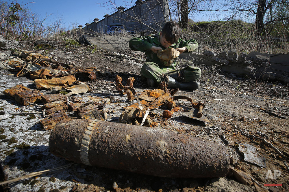 In this photo taken on Monday, May  2, 2016, Gosha, 10-year-old son of a member of a  volunteer group searching for the remains of Soviet soldiers killed during WWII, tries to put on an uncovered WWII Soviet gas mask at at Nevsky Pyatachok near Kirovsk,  Russia. Nevsky Pyatachok, an area about 50 kilometers (30 miles) southeast of St. Petersburg, has proved especially fertile ground. As many as 200,000 Soviet soldiers were killed here between September 1941 and May 1943 in fighting to break the Nazi siege of the city, which was then called Leningrad. (AP Photo/Dmitri Lovetsky)