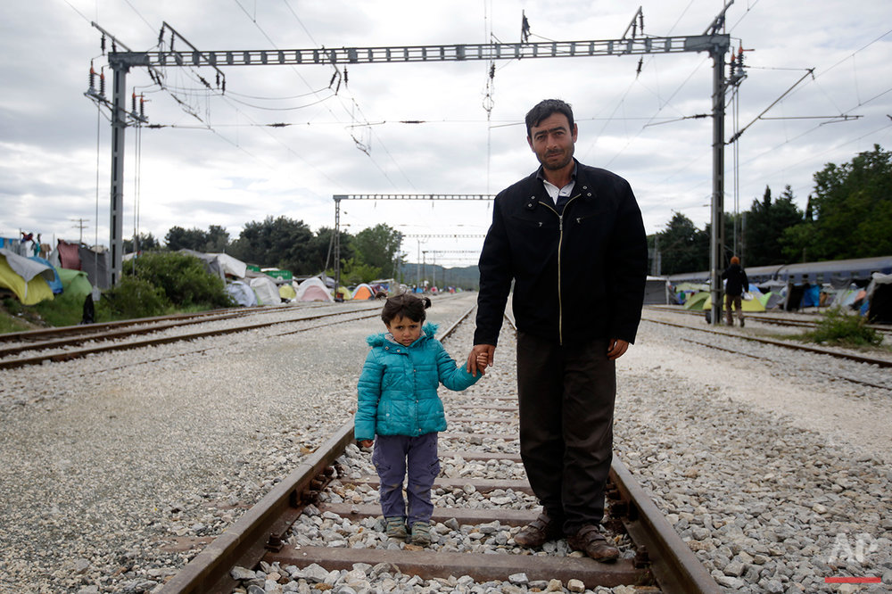 Adid Al Barum, right, holds the hand of his 4-year-old daughter Ala, as they pose for a portrait on the tracks of a rail way station which was turned into a makeshift camp crowded by migrants and refugees at the northern Greek border point of Idomeni, Greece, Tuesday, May 3, 2016. (AP Photo/Gregorio Borgia)