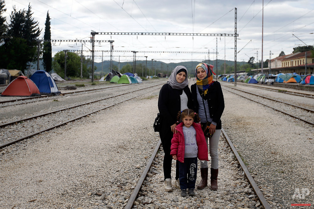 Syrian Magdolin Hameidi, left, poses for a portrait with her friend Juanin Ala, and her daughter Jana, 5 years old, on the tracks of a rail way station which was turned into a makeshift camp crowded by migrants and refugees at the northern Greek border point of Idomeni, Greece, Tuesday, May 3, 2016. At Greece's blockaded border with Macedonia, 10,000 people who arrived hoping to start new lives farther west and north in Europe are settling instead into lives in limbo, sleeping in tents in mud and rain as they wait to find out what happens next. (AP Photo/Gregorio Borgia)