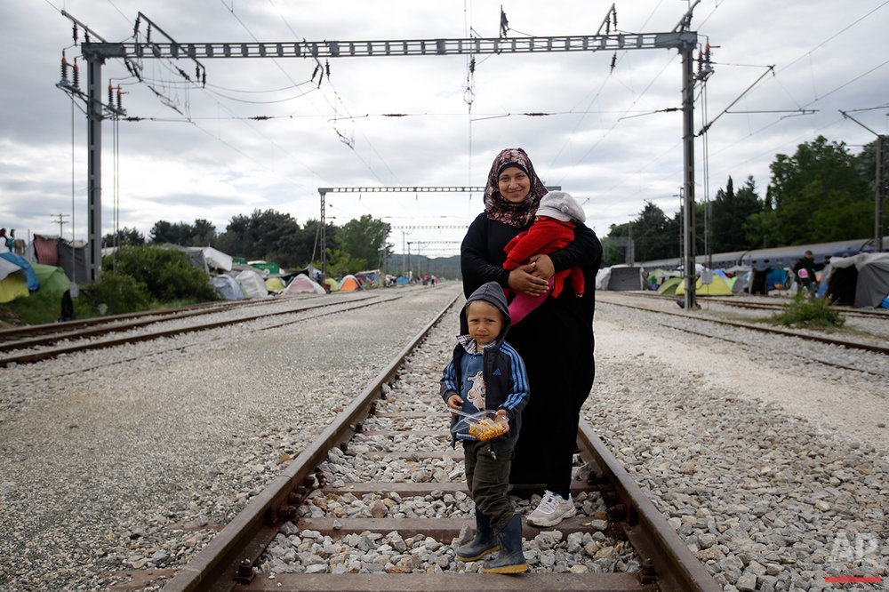 Syria's Mariam Shaudi, holds her 4-month-old baby, Aia, as she poses for a portrait together with her 5-year-old son Ali, on the tracks of a rail way station which was turned into a makeshift camp crowded by migrants and refugees at the northern Greek border point of Idomeni, Greece, Tuesday, May 3, 2016.  (AP Photo/Gregorio Borgia)