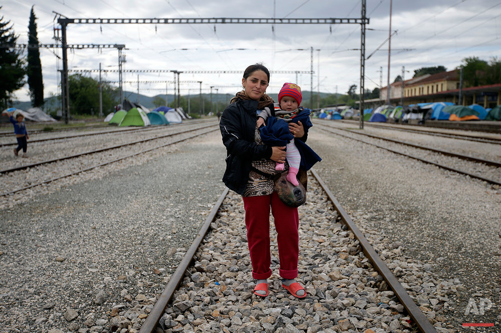 Diliber Kelesh from Syria, holds her 6-month-old baby Kamira as she poses for a portrait on the tracks of a rail way station which was turned into a makeshift camp crowded by migrants and refugees at the northern Greek border point of Idomeni, Greece, Tuesday, May 3, 2016.  (AP Photo/Gregorio Borgia)