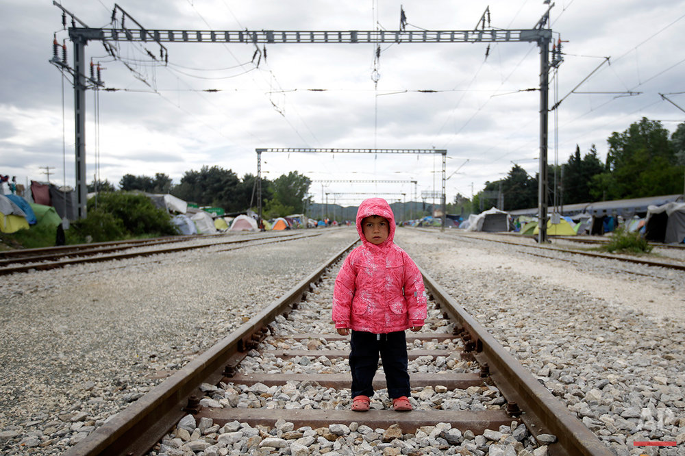 Lamal Alil, 3 years old, from Syria, poses for a portrait on the tracks of a rail way station which was turned into a makeshift camp crowded by migrants and refugees at the northern Greek border point of Idomeni, Greece, Tuesday, May 3, 2016.  (AP Photo/Gregorio Borgia)
