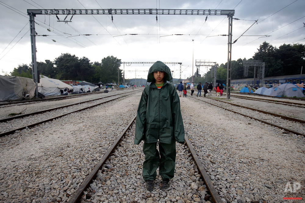 Rostani, 10, from Afghanistan, wears a rain jacket and trousers as he poses for a portrait on the tracks of a rail way station which was turned into a makeshift camp crowded by migrants and refugees at the northern Greek border point of Idomeni, Greece, Tuesday, May 3, 2016. At Greece's blockaded border with Macedonia, 10,000 people who arrived hoping to start new lives farther west and north in Europe are settling instead into lives in limbo, sleeping in tents in mud and rain as they wait to find out what happens next.  (AP Photo/Gregorio Borgia)