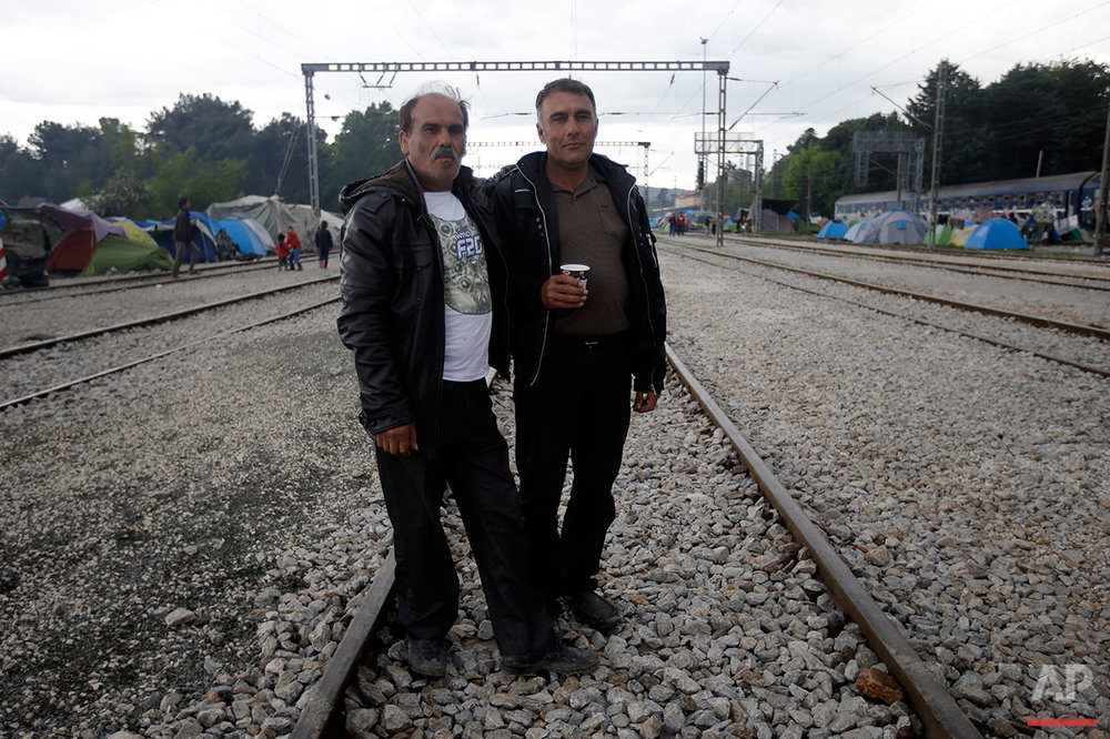 Syrians Murdin Mamou, left, and Mohammed Juma pose for a portrait on the tracks of a rail way station which was turned into a makeshift camp crowded by migrants and refugees at the northern Greek border point of Idomeni, Greece, Tuesday, May 3, 2016. At Greece's blockaded border with Macedonia, 10,000 people who arrived hoping to start new lives farther west and north in Europe are settling instead into lives in limbo, sleeping in tents in mud and rain as they wait to find out what happens next. (AP Photo/Gregorio Borgia)