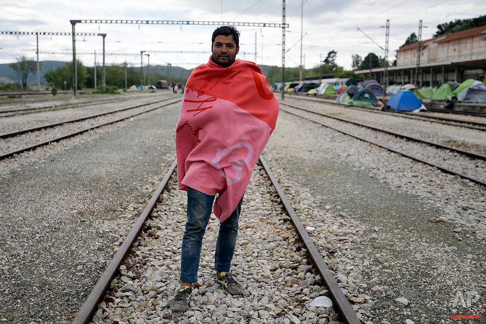 Maleem Sadiq from Pakistan, poses for a portrait on the tracks of a rail way station which was turned into a makeshift camp crowded by migrants and refugees at the northern Greek border point of Idomeni, Greece, Tuesday, May 3, 2016. Many thousands of migrants remain at the Greek border with Macedonia, hoping that the border crossing will reopen, allowing them to move north into central Europe. (AP Photo/Gregorio Borgia)