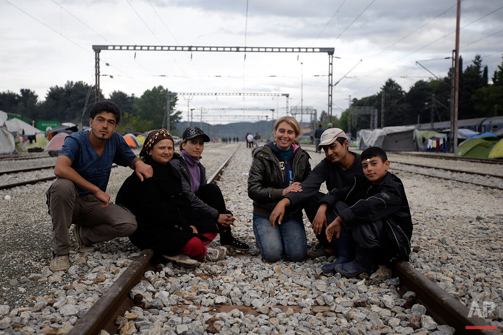From left, Rashid Hassan, Waida Hassan, Evin Bilel, Neda Bilel, Hamud Hawar and Mohammed Arous, all from Syria, pose for a portrait on the tracks of a rail way station which was turned into a makeshift camp crowded by migrants and refugees at the northern Greek border point of Idomeni, Greece, Tuesday, May 3, 2016.  (AP Photo/Gregorio Borgia)