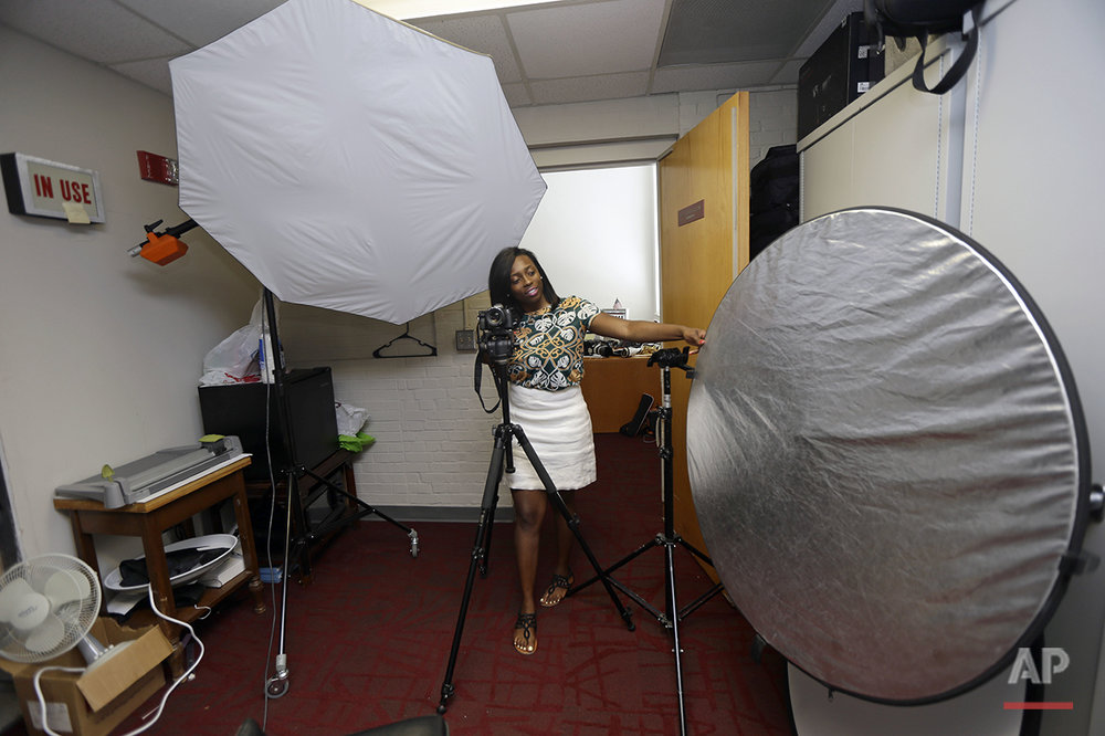 Briana Lawrence, 21, works on her lighting skills in a photo and video studio at North Carolina Central University in Durham, N.C., on Thursday, July 14, 2016. With $40,000 in student debt, she's working hard to establish her own cosmetic business after graduating. She plans to vote for Hillary Clinton, but feels America has lost its way. (AP Photo/Gerry Broome)