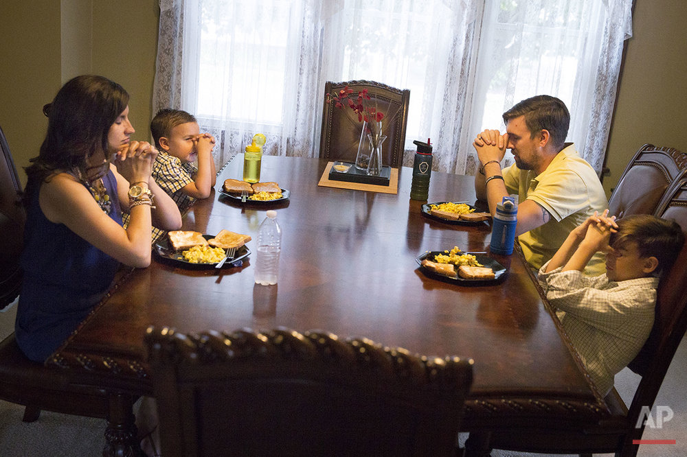 "Kristi Clay, left, and her husband, Bill, second from right, pray before a meal with their sons, Ami, second from left, and Xavier, at their home in Ashville, Ohio., on Saturday, July 9, 2016. Their strong Christian faith has not helped him find much inspiration in the current presidential candidates, both of whom Bill sees as self-serving and unwilling to budge on important issues. Although they both plan to vote, he says, ""I'm feeling a little pessimistic this year."" (AP Photo/John Minchillo)"