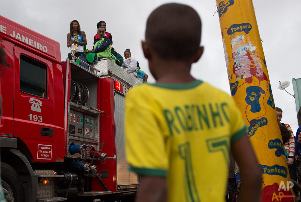 "A child watches as Brazilian judo gold medalist Rafaela Silva is given a hero's welcome as she rides a fire truck into the Cidade de Deus ""City of God"" slum in Rio de Janeiro, Brazil, Monday, Aug. 22, 2016. Silva who grew up in the violent, poverty stricken slum, won special mention from IOC president Thomas Bach, saying she's an inspiration across the world."" (AP Photo/Leo Correa)"