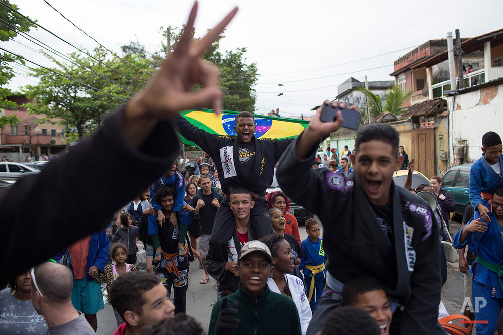 "Youths wearing kimonos cheer as Brazilian judo gold medalist Rafaela Silva is given a hero's welcome into the Cidade de Deus ""City of God"" slum in Rio de Janeiro, Brazil, Monday, Aug. 22, 2016. Silva who grew up in the violent, poverty stricken slum, won special mention from IOC president Thomas Bach, saying she's an inspiration across the world."" (AP Photo/Leo Correa)"