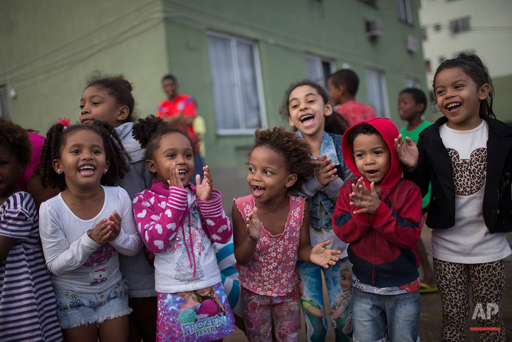 "Children cheer as Brazilian judo gold medalist Rafaela Silva is given a hero's welcome as she rides a fire truck into the Cidade de Deus ""City of God"" slum in Rio de Janeiro, Brazil, Monday, Aug. 22, 2016. Silva who grew up in the violent, poverty stricken slum, won special mention from IOC president Thomas Bach, saying she's an inspiration across the world."" (AP Photo/Leo Correa)"