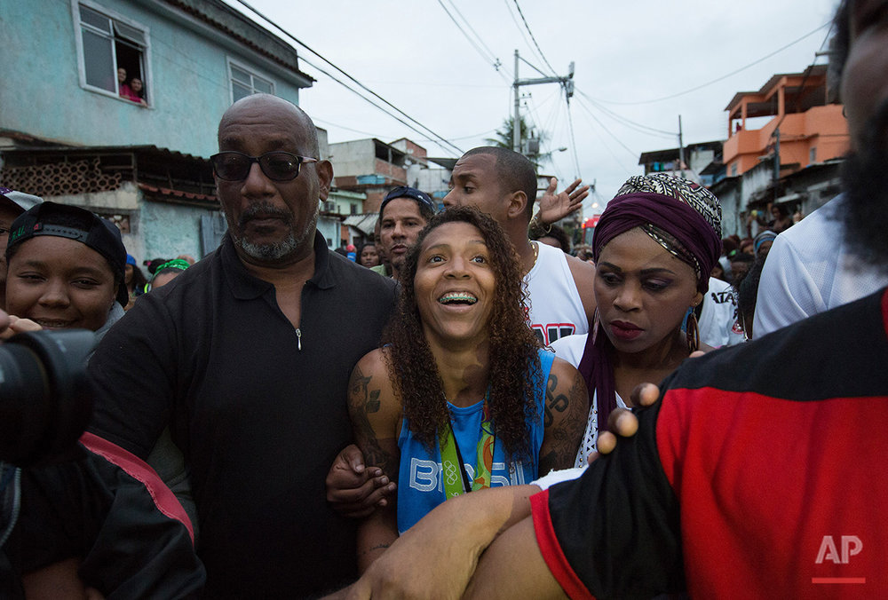 "Brazilian Judo gold medalist Rafaela Silva, center, arrives to the street where she used to live in the Cidade de Deus ""City of God"" slum in Rio de Janeiro, Brazil, Monday, Aug. 22, 2016. Silva who grew up in the violent, poverty stricken slum, won special mention from IOC president Thomas Bach, saying she's an inspiration across the world."" (AP Photo/Leo Correa)"