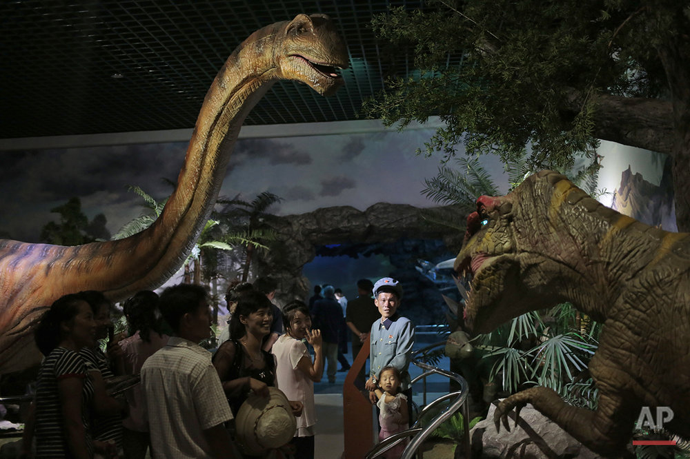 North Koreans look at models of dinosaurs at the Natural History Museum, part of the newly opened Pyongyang Central Zoo in Pyongyang, North Korea, Tuesday, Aug. 23, 2016. North Korean leader Kim Jong Un's latest gift to the lucky residents of Pyongyang, the renovated central zoo, is pulling in thousands of visitors a day with a slew of attractions ranging from such typical zoo fare as elephants, giraffes, penguins and monkeys to a high-tech natural history museum. (AP Photo/Dita Alangkara)