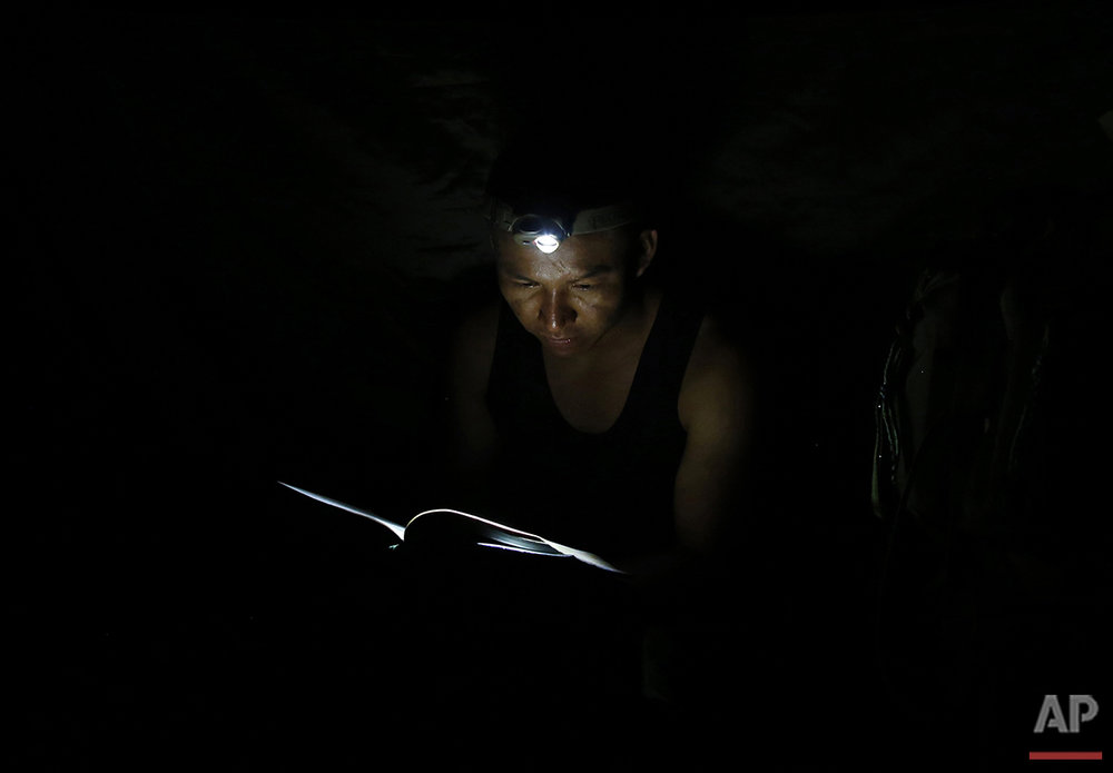 In this Aug. 11, 2016 photo, a rebel soldier of the 48th Front of the Revolutionary Armed Forces of Colombia, or FARC, uses a head lamp to for some late-night reading at a FARC encampment in the southern jungles of Putumayo, Colombia. The soldier is reading a compilation of the late guerrilla leader Manuel Marulanda Velez's diary and correspondence. (AP Photo/Fernando Vergara)