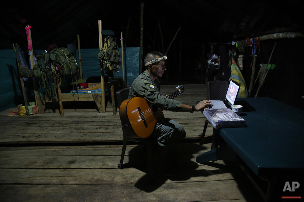 In this Aug. 11, 2016 photo, Manuel, a mid-level commander for the 48th Front of the Revolutionary Armed Forces of Colombia, or FARC, learns to play his guitar via the internet at a FARC encampment in the southern jungles of Putumayo, Colombia. The camp provides regular access to the internet for commanders. (AP Photo/Fernando Vergara)