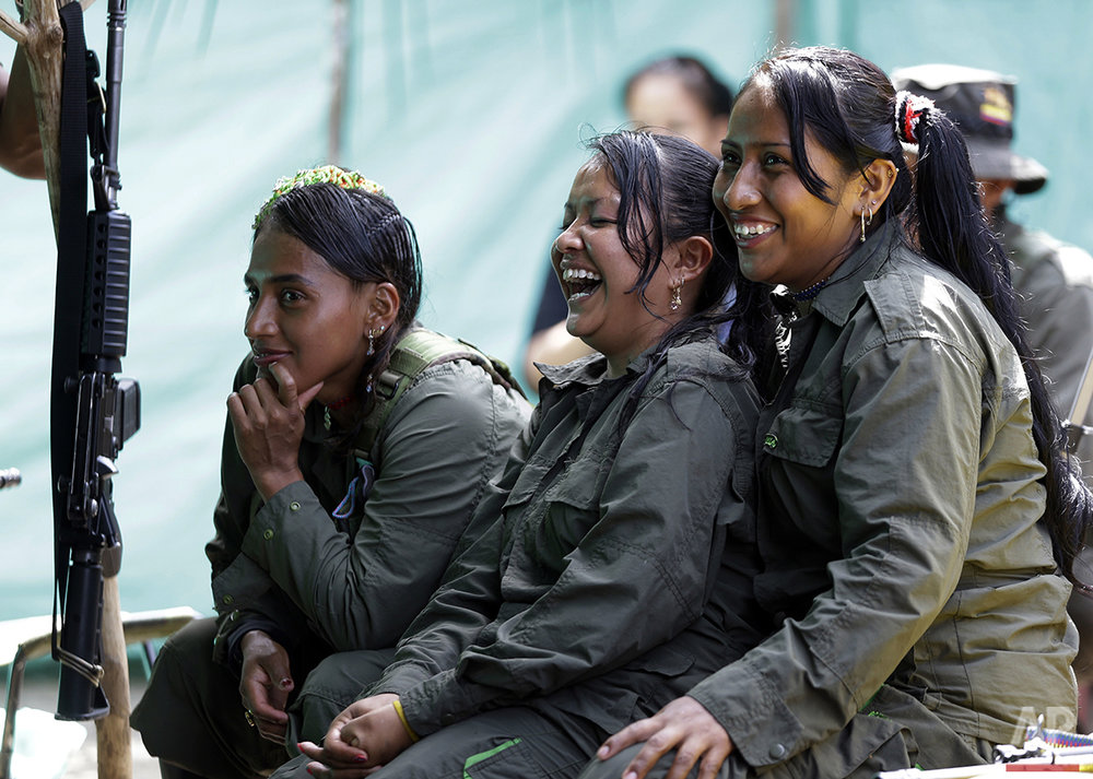 In this Aug. 11, 2016 photo, rebels of the 32nd Front of the Revolutionary Armed Forces of Colombia, or FARC, laugh during a break, at their camp in the southern jungles of Putumayo, Colombia. As Colombia's half-century conflict winds down, with the signing of a peace deal perhaps just days away, thousands of FARC rebels are emerging from their hideouts and preparing for a life without arms. (AP Photo/Fernando Vergara)