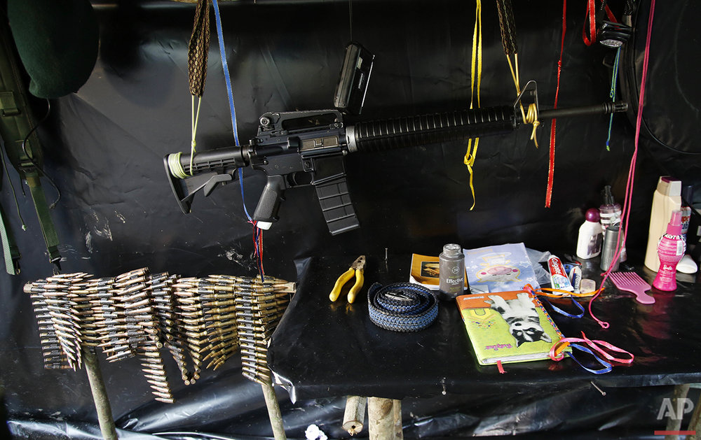 In this Aug. 11, 2016 photo, an assault rifle hangs in the tent of the 48th Front of the Revolutionary Armed Forces of Colombia, or FARC, in the southern jungles of Putumayo, Colombia. The FARC's southern bloc is one of the rebel army's oldest and most belligerent fighting units. (AP Photo/Fernando Vergara)
