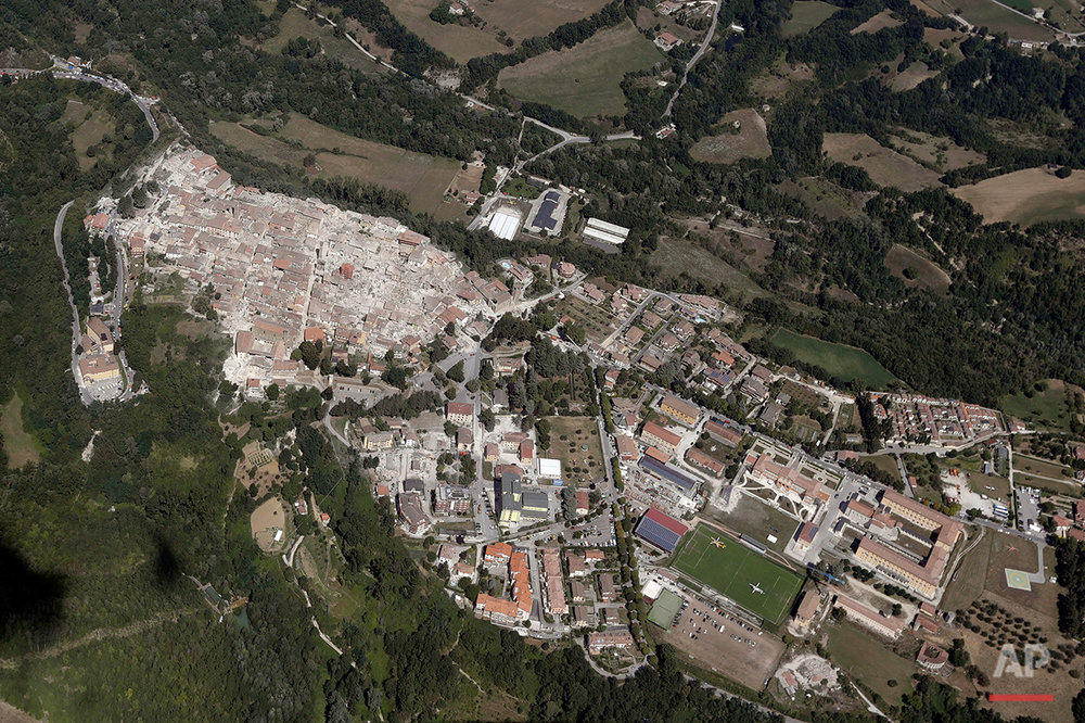 This aerial photo shows the damaged buildings in the historical center of the town of Amatrice, left part of the town, in central Italy, after an earthquake, Aug. 24, 2016. (AP Photo/Gregorio Borgia)