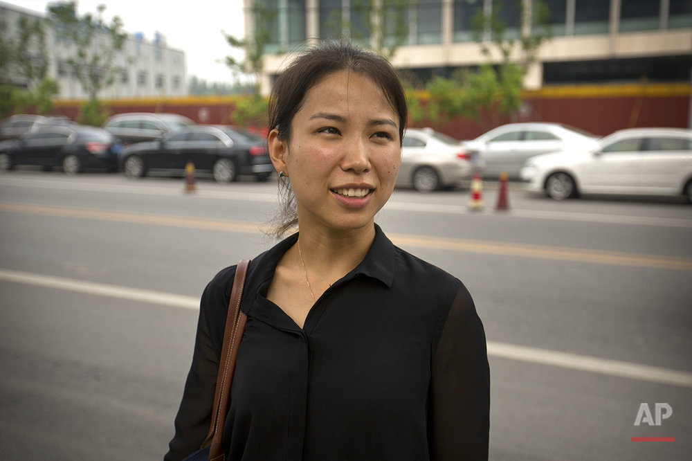 "Liu Xiaodan, 30, a hotel manager, stands outside the U.S. embassy in Beijing on Friday, July 29, 2016. Of Americans, she says, ""I think the way they are talking and dealing with personal relations is quite direct. They just like speaking their mind, which is a reason that I don't feel quite comfortable going around with Americans."" (AP Photo/Mark Schiefelbein)"