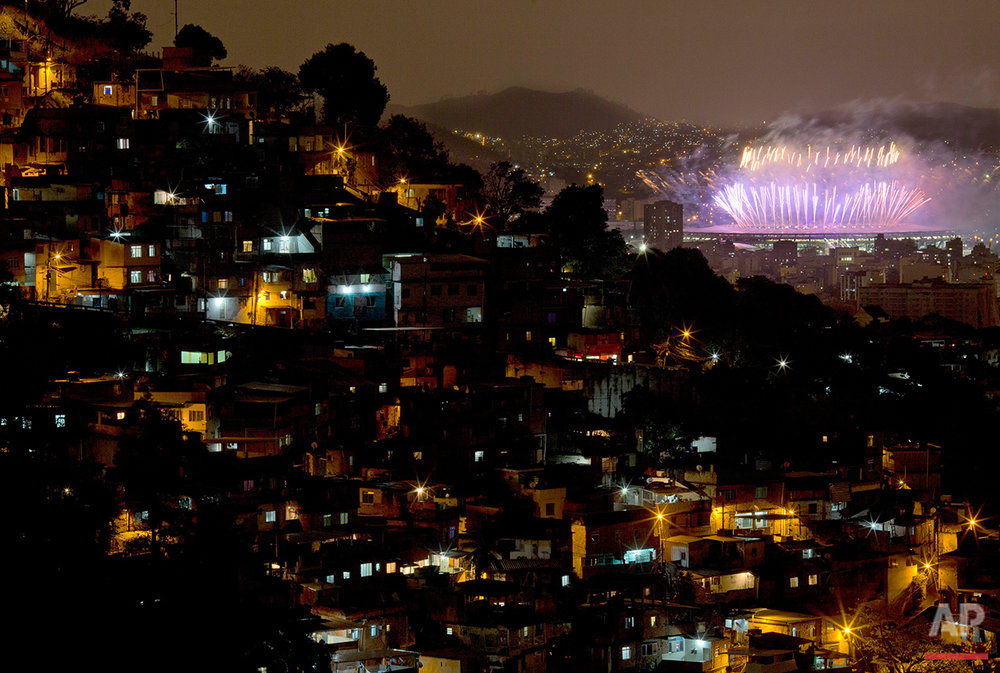 With the Morro dos Prazeres slum in the foreground, fireworks explode over the Maracana stadium during the closing ceremony of the 2016 Summer Olympic Games in Rio de Janeiro, Brazil, Sunday Aug. 21, 2016.(AP Photo/Leo Correa)