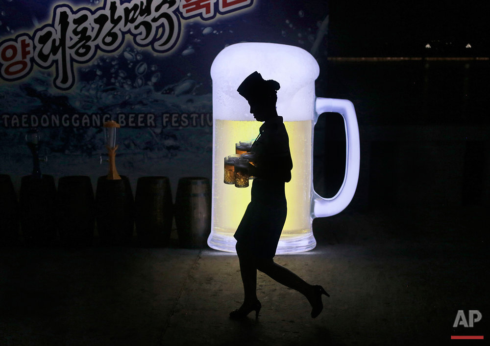 A waitress walks past an advertisement as she carries mugs of beer during Taedonggang Beer Festival in Pyongyang, North Korea, Sunday, Aug. 21, 2016. The festival, the first of its kind in the country, was held as a promotional event for the locally brewed beer. (AP Photo/Dita Alangkara)