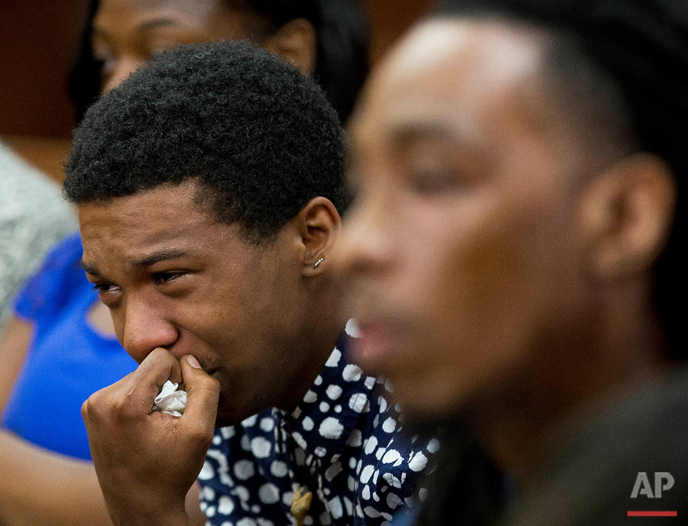 Marquez Tolbert cries Tuesday, Aug. 23, 2016 as he listens in Atlanta to testimony in the trial of Martin Blackwell who is accused of pouring boiling water on him and his friend, Anthony Gooden, right, as they slept. The FBI has decided not to pursue hate crime charges against Blackwell, found guilty of throwing scalding water on the sleeping gay couple. (AP Photo/John Bazemore)