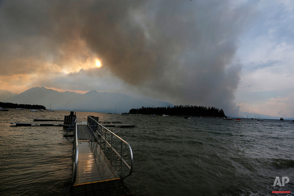 A wildfire is visible from Leek's Marina on the shore of Jackson Lake, in Grand Teton National Park, Wyo., Wednesday, Aug. 24, 2016. (AP Photo/Brennan Linsley)