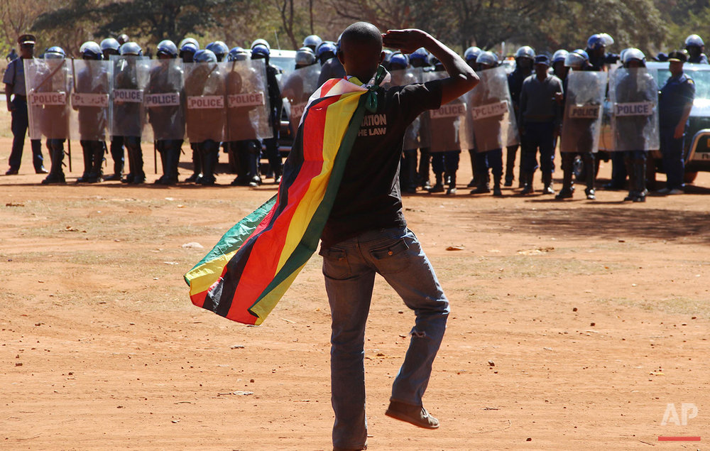 A man wearing a Zimbabwean flag salutes riot police during a protest in Harare, Zimbabwe, on Friday, Aug. 26, 2016. The demonstration organized by opposition political parties calling for reforms, is the first time that the fractured opposition has joined forces in a single unified action to confront President Robert Mugabe's government. (AP Photo)