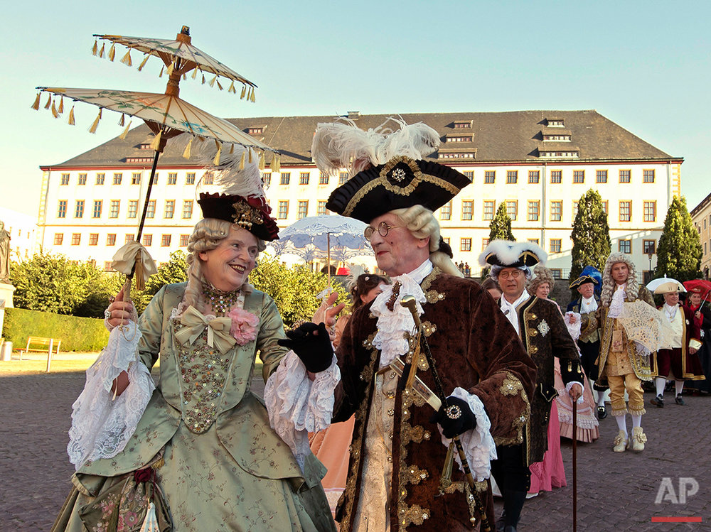 People dressed in Baroque costumes walk in front of the Friedenstein Castle during the opening of the Baroque Festival in Gotha, Germany, Friday, Aug. 26, 2016. The castle is the larges German early Baroque palace complex from the 17th century. (AP Photo/Jens Meyer)