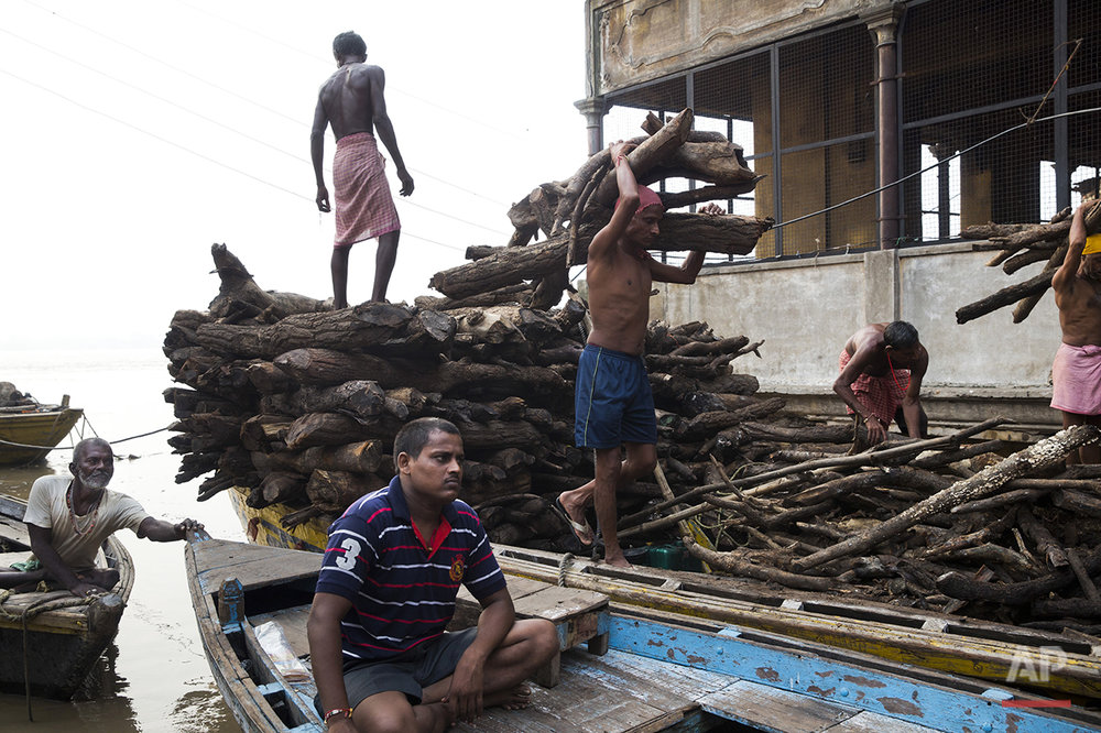 Indian workers at a crematorium transfer woods to a dry place at Manikarnika Ghat in Varanasi, India, Saturday, Aug. 27, 2016. As the mighty Ganges River overflowed its banks this past week following heavy monsoon rains, large parts of the Hindu holy town of Varanasi were submerged by floodwaters, keeping away thousands of Hindu devotees. Varanasi is a pilgrim town that Hindus visit to take a dip in the holy Ganges. (AP Photo/Tsering Topgyal)