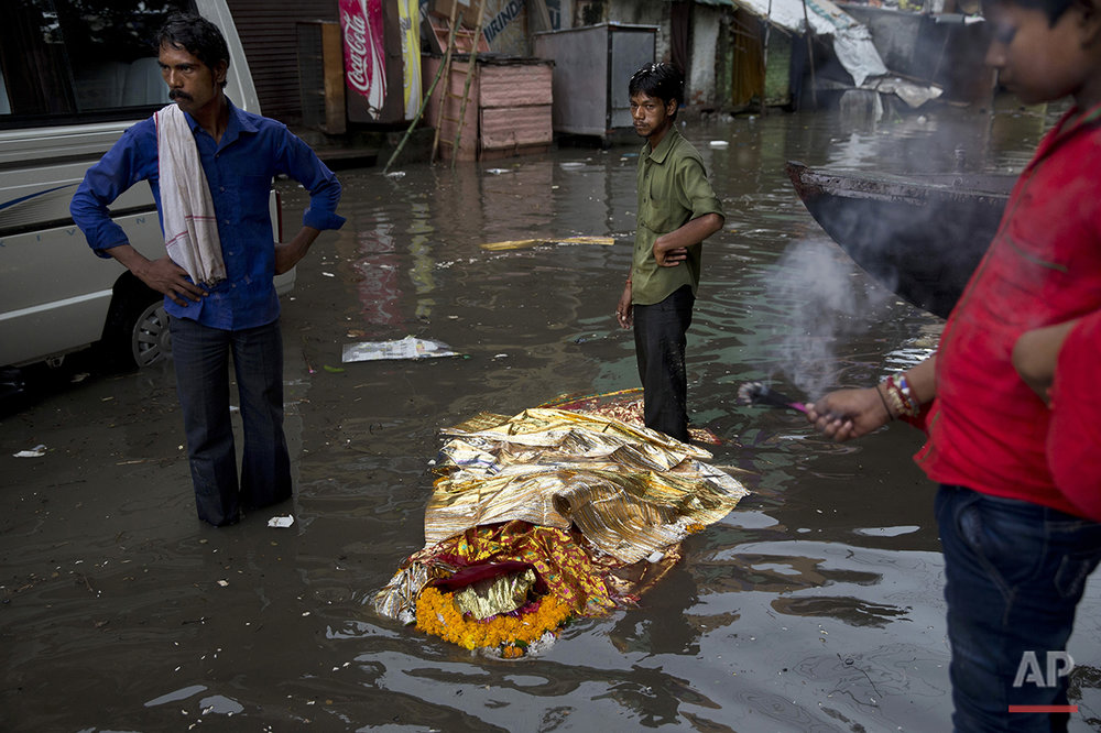 In this Friday, Aug. 26, 2016 photo, a dead body lies in a flooded street before performing a Hindu funeral at the Harishchandra Ghat in Varanasi, India. As the mighty Ganges River overflowed its banks this past week following heavy monsoon rains, large parts of the Hindu holy town of Varanasi were submerged by floodwaters, keeping away thousands of Hindu devotees. Varanasi is a pilgrim town that Hindus visit to take a dip in the holy Ganges. (AP Photo/Tsering Topgyal)
